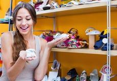 Stående av kvinnan som sköter par av skor för unge Royaltyfria Foton