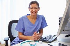 Stående av kvinnlig doktor In Office Working på datoren Arkivbilder