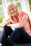 Stående av åldrigt kvinnasammanträde för mitt på fönstret Seat Arkivbild