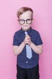Stående av lite att le pojken i roligt exponeringsglas och band skola förträning Mode Studiostående över rosa bakgrund Royaltyfri Bild