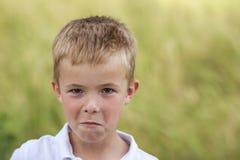 Stående av lite den missnöjda och missbelåtna pojken med guld- Arkivfoto
