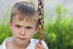 Stående av lite den missnöjda och missbelåtna pojken med guld- Arkivfoton