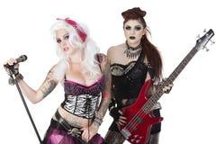 Stående av punkrockmusiker med den elektriska gitarren och mikrofonen över vit bakgrund Royaltyfri Fotografi