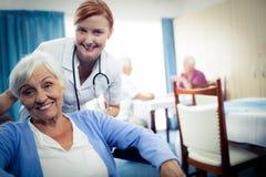 Stående av sjuksköterskan med en hög kvinna Fotografering för Bildbyråer