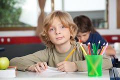 Stående av skolpojkehandstil i bok på skrivbordet Arkivbilder