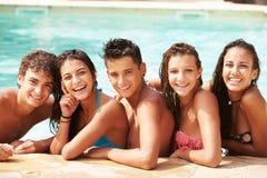 Stående av tonårs- vänner som har gyckel i simbassäng Royaltyfri Bild