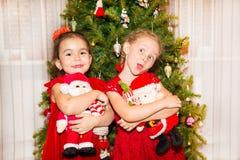 Stående av två barnflickor runt om en dekorerad julgran Unge på nytt år för ferie Royaltyfri Foto