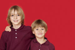 Stående av två lyckliga bröder mot röd bakgrund Royaltyfri Foto