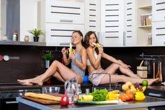 Stående av två tvilling- systrar som har gyckel i morgonen som förbereder frukosten Arkivbilder