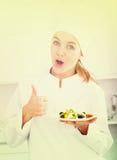 Stående av ung sallad för coosiekvinnavisning på kök Royaltyfri Bild