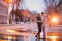 Stående av unga härliga par som kysser i en regnig dag för höst Arkivbild