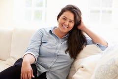 Stående av överviktigt kvinnasammanträde på soffan Arkivfoton