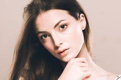 Stående för skönhetkvinnaframsida Härlig brunnsortmodellflicka med perfekt ny ren hud över beige bakgrund Arkivfoton