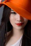 Stående som är nära upp av härlig asiatisk kvinnamodell i orange remsa Arkivfoton