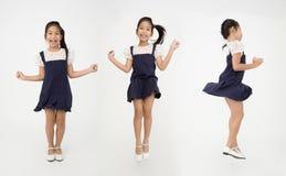 Ståendegruppen av den asiatiska gulliga flickan hoppar med leendeframsidan Arkivbilder
