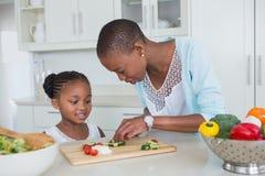 Ståendemoder och dotter som tillsammans gör en sallad Arkivbild
