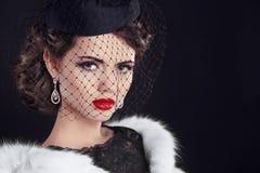 Ståenden av av den eleganta retro kvinnan som bär den lilla hatten med, skyler Royaltyfria Bilder