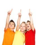 Ståenden av de lyckliga barnen pekar vid fingrar upp - isolerat på Arkivbilder