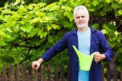Ståenden av den höga mannen med att bevattna kan i trädgård Arkivfoto