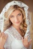 Ståenden av den härliga bruden som bär i klassisk vit, skyler r Royaltyfri Foto