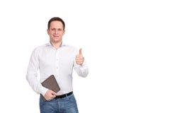Ståenden av den lyckliga le unga affärsmannen med den bruna mappen, shower tummar upp tecken på vit bakgrund Arkivbilder