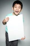 Ståenden av det asiatiska barnet med den tomma plattan för tillfogar din text. Royaltyfri Foto