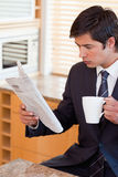 Ståenden av en dricka tea för affärsman fördriver läsning nyheterna Royaltyfri Fotografi