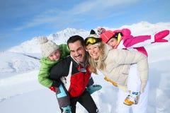 Ståenden av en glad familj skidar in semesterorten Arkivbilder