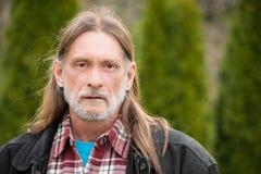 En mitt åldras man med långt hår Fotografering för Bildbyråer