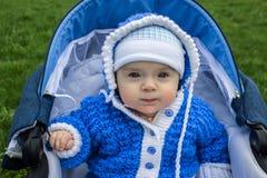 Ståenden av gulligt behandla som ett barn sammanträde i sittvagn Åldern av behandla som ett barn är 6 månader Arkivbild