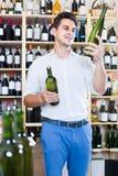 Ståenden av mannen som väljer flaskan av vin shoppar in Arkivbilder