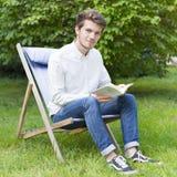 Ståenden av sammanträde uppsökte den unga mannen i den gröna trädgården Arkivfoto