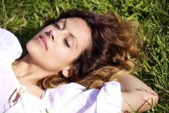 Stenditura di sonno della giovane donna sull'erba Immagini Stock Libere da Diritti