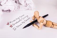 Stenditura fantasticando la bambola congiunta di legno del manichino che tiene una lista di controllo nera di istruzione della pe immagini stock