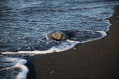 Stenen badade vid vågor på en strand i Kalifornien Royaltyfri Bild