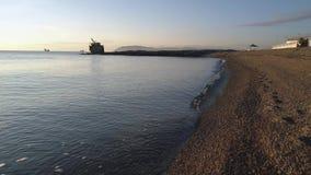 Stenen bij strand en het zeewater schot Het strand van de kiezelsteen bij zonsondergang Strandscène met vele kiezelstenen in de d stock videobeelden