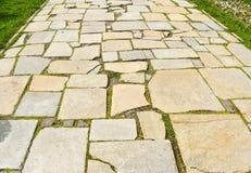 Stenen blockerar trottoar i staden parkerar Bana som göras med stora asymmetriska stenar arkivfoto