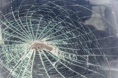 Stenen eller en kullersten slog vindrutan, som den flög in i bilen på hastighet fragmenterar och spårar av en bruten vindruta, te royaltyfri bild
