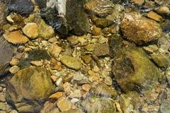 Stenen en kiezelstenen onder water Stock Foto