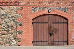 Stenen en rode bakstenen muur met houten deur royalty-vrije stock afbeelding
