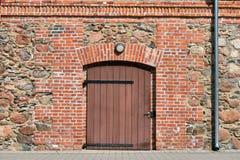 Stenen en rode bakstenen muur met houten deur royalty-vrije stock foto's