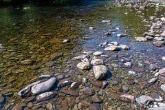 Stenen en rotsen op de bank van ondiepe stroom royalty-vrije stock afbeeldingen