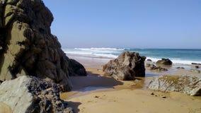Stenen en rotsen op zandig strand in Portugal de West-Atlantische Oceaan stock videobeelden