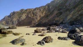Stenen en rotsen op zandig strand in Portugal de West-Atlantische Oceaan stock video
