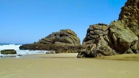 Stenen en rotsen op zandig strand in Portugal de West-Atlantische Oceaan stock footage
