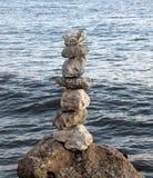 Stenen evenwichtig op de kust stock foto's