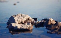Stenen, halve status in de kalme waterspiegel stock foto's