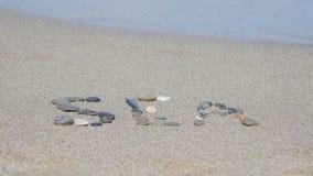 Stenen in het zand door het overzees stock footage
