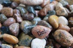Stenen med ` gör! ` Som är skriftlig på den Arkivfoto