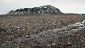 Stenen na het smelten van ijs en sneeuw op achtergrond van berg in Svalbard stock footage